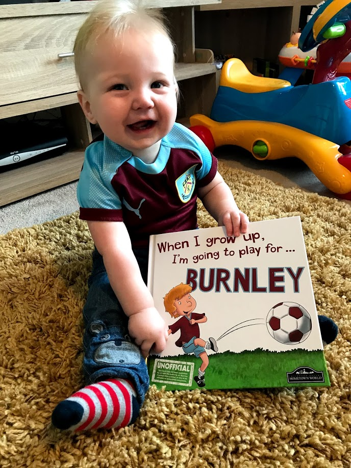 Noah in his Burnley FC shirt with his Burnley book.